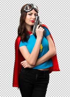 Pretty superhero girl holding a pistol