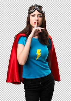 Pretty superhero girl making silence gesture