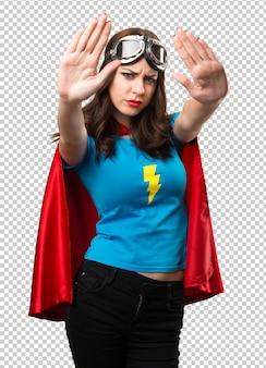 Pretty superhero girl making stop sign