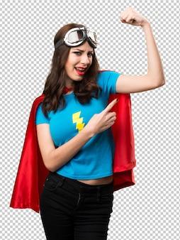 Милая девушка супергероя делая сильный жест