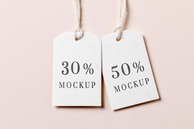 Price tag with discount  on pink background flat lay