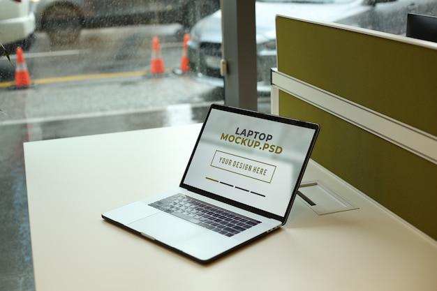 オフィスのモックアップpsdで職場のテーブルの上のノートパソコン