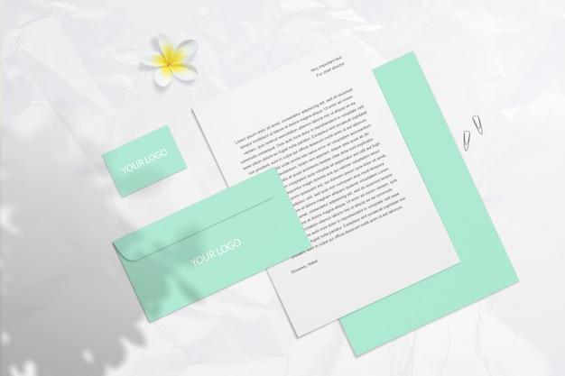 Летом пустой брендинг макет с мятой визитные карточки, конверты, изолированные на светлой поверхности с цветком и тени. psd умный слой может двигаться