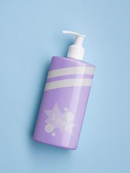 Бутылка фиолетового жидкого мыла на синем фоне