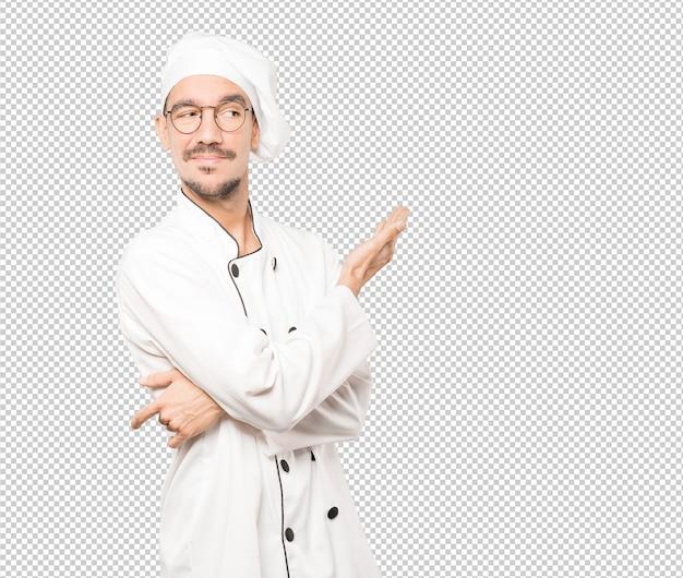 Озадаченный молодой повар делает жест не понимаю