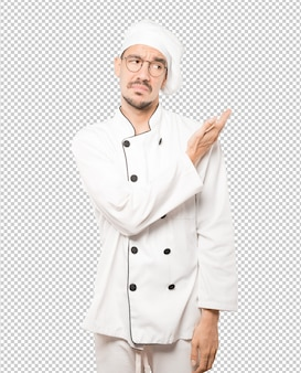 Puzzled young chef doing a gesture of not understand