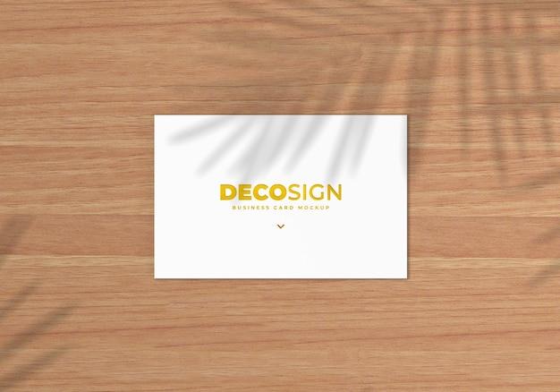 木製のテーブルにリアルな名刺ロゴのモックアップ