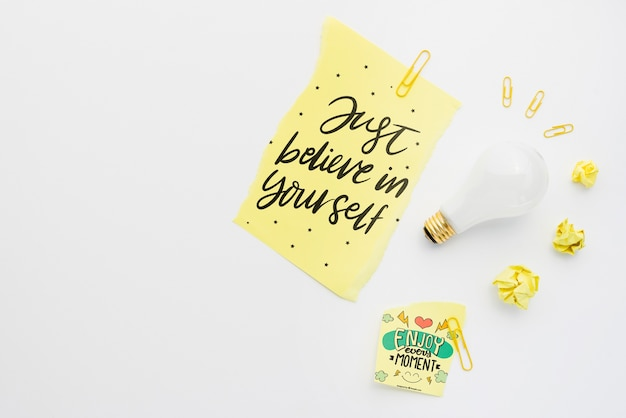 Realistic light bulb with just believe in yourself quote on paper