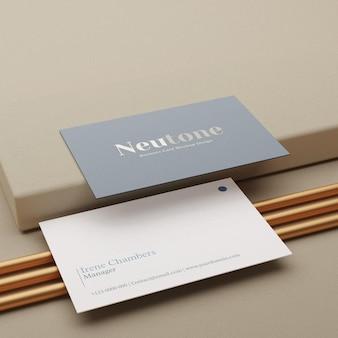 Реалистичный минимальный макет визитки на пьедестале и золотой палке