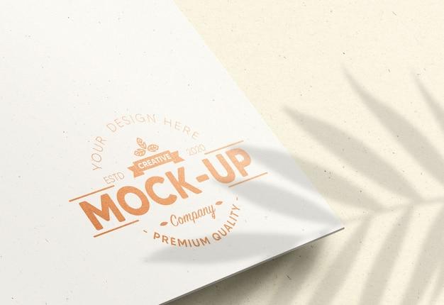 ブロンズフォイル効果のある白い紙のリアルなモックアップロゴ