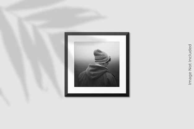 Realistic square frame mockup hanging on wall with shadow overlay