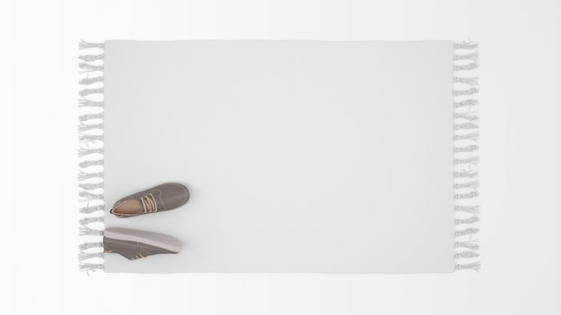 Realistic white carpet with a pair of shoes on top view