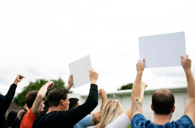Вид сзади активистов, показывающих бумаги во время протеста
