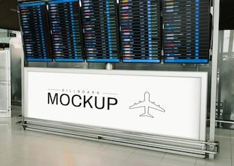 Rectangular billboard mockup under a departure and arrival display board