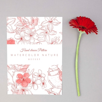 Red gerbera flower placed next to card mockup