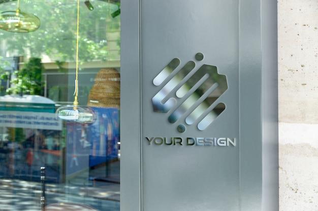 Отражающий металлический логотип на витрине магазина