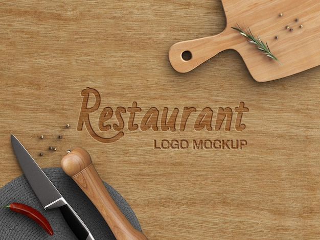Restaurant logo mockup cooking concept carved on wood table with kitchenware top view isolated