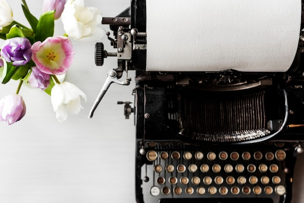 Retro typewriter machine with paper by flowers in vase