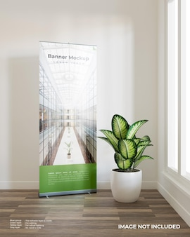 Roll up banner mockup with a plant beside the window