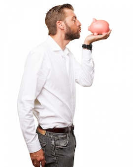Romantic guy kissing his piggy bank
