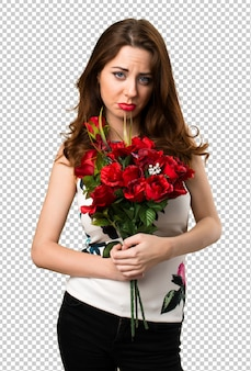Sad beautiful young girl holding flowers