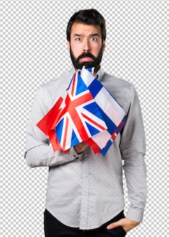 Sad handsome man with beard holding many flags
