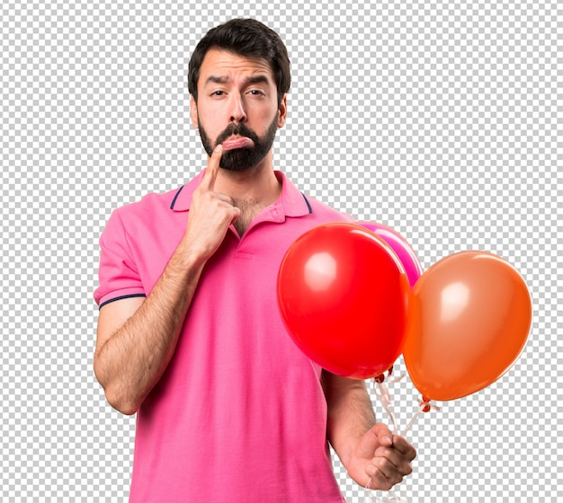 Sad handsome young man holding balloons
