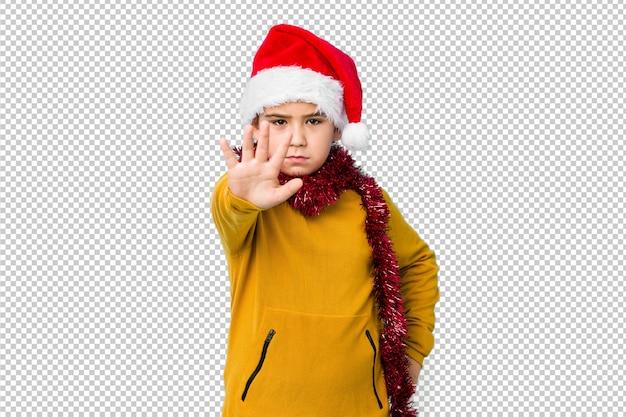 Мальчик празднуя рождество нося шляпу santa изолировал положение при протягиванный знак стопа показа руки, предотвращая вас.