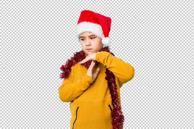 Мальчик празднуя рождество нося шляпу santa изолировал показывать жест перерыва.