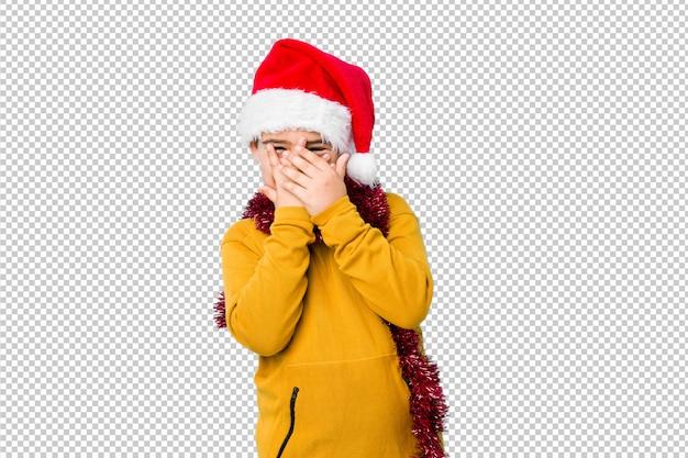 Мальчик празднуя рождество нося шляпу santa изолировал мерцание через пальцы испуганные и нервный.