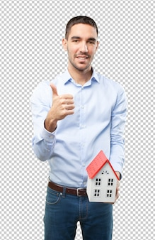 Satisfied young man holding a small house
