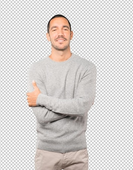 Satisfied young man with crossed arms gesture
