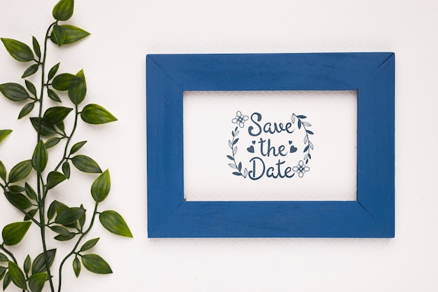 Save the date mock-up dark blue frame and plant