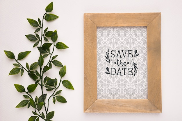 Save the date mock-up wooden frame and plant