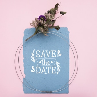 Сохраните макет даты на синей бумаге и сухих цветах