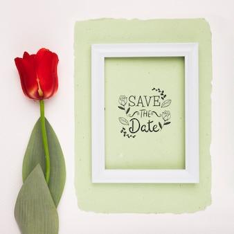 日付のモックアップ額縁とチューリップの花を保存する