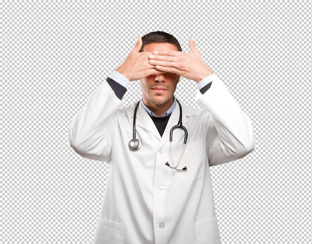Scared doctor covering his eyes against white background