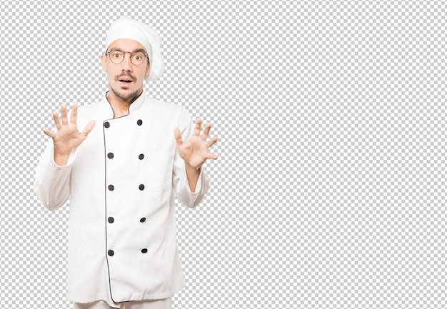 Scared young chef screaming against background