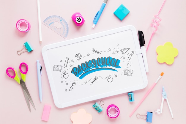 School supplies with white board on pink background