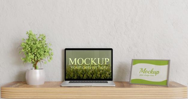 木製の机の上のノートパソコンのモックアップとフレームのモックアップを画面します。
