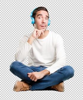 ヘッドフォンを使用して疑わしい若い男を座らせる