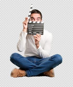 Сидящий счастливый молодой человек с помощью clapperboard