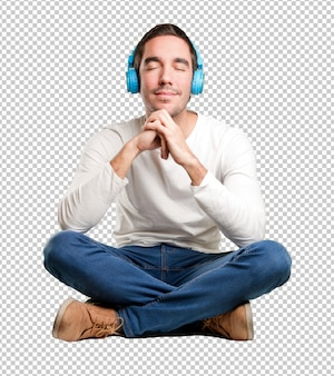 ヘッドフォンを使って座っている幸せな若い男