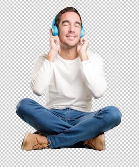 Сидящий счастливый молодой человек с помощью наушников