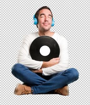 ヘッドフォンを使って座っている幸せな若い男 Premium Psd