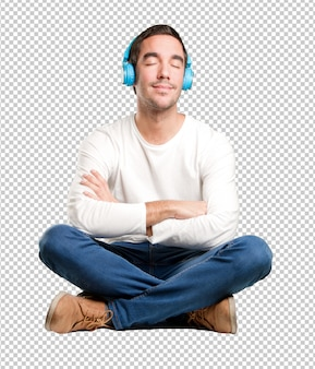 Seated happy young man using a headphones