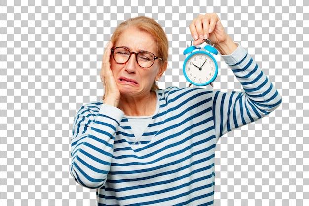 目覚まし時計を持つシニアの美しい女性