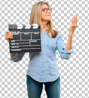 Senior beautiful woman with a cinema clapper