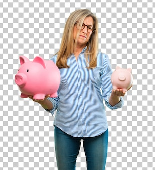 Senior beautiful woman with a piggy bank