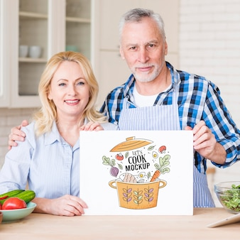 Senior couple in kitchen holding cardboard mock-up